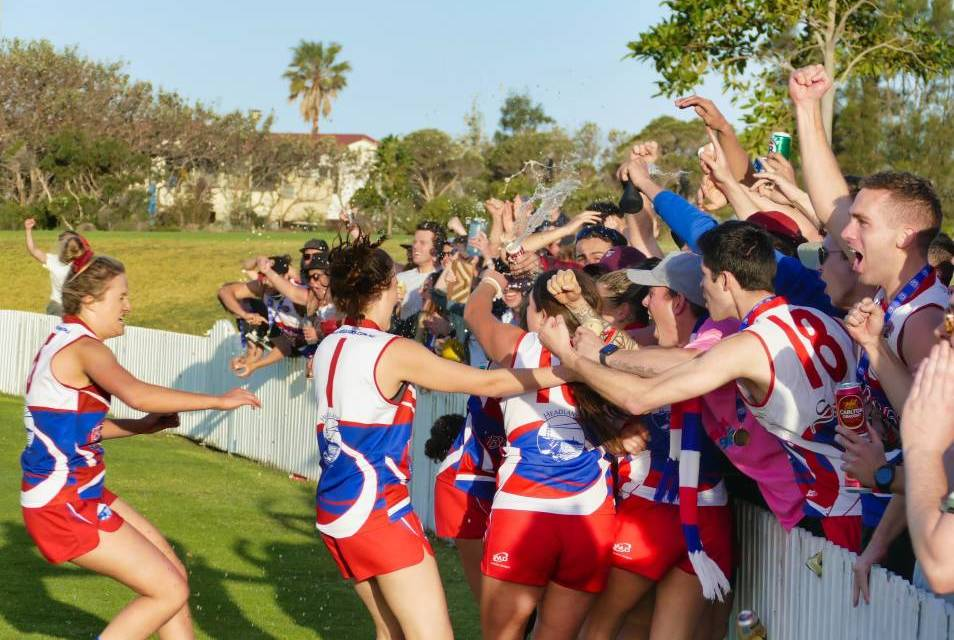 Bulldogs women's players and supporters embrace after Wollongong won last year's title. The club's 2020 season opener was called off due to precautionary reasons over a COVID-19 scare. Photo: Dave Johnson/AFL South Coast