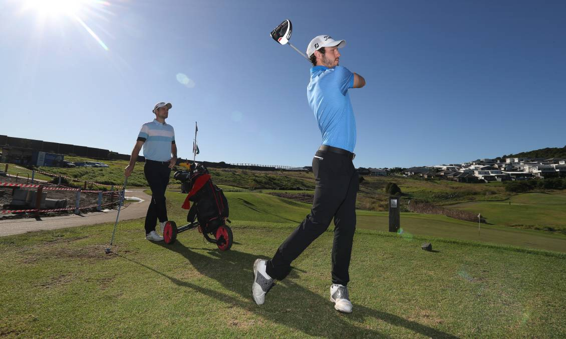 Kyle Zunic tees off as older brother Jordan watches on at Shell Cove Links. Photo: Robert Peet