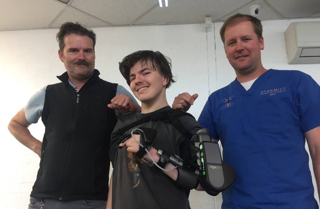 BIONIC MAN: Nineteen-year-old Khy Antoniazzo with his new MyoPro powered arm with his caseworker/physiotherapist Damien Barratt (left) and Jens Baufeldt, of Extremity Prosthetics and Orthotics in Nowra.