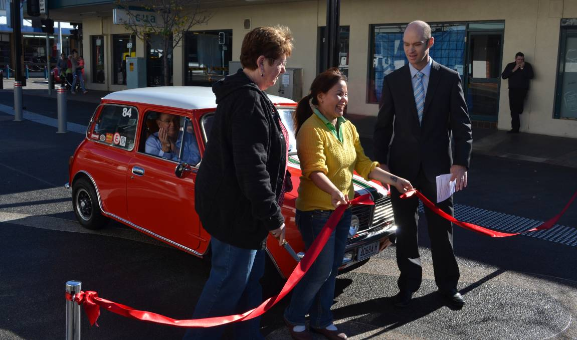 OFFCIAL: Shoalhaven City Council director of assets works Ben Stewart invited business owners Anne Snow from Anne's Second Hand Book Shop and Deb Trinh from Nowra Village Hot Bake to cut the red ribbon and declare Junction Court open to traffic as excited motoring enthusiast Wayne Brighton readied his red mini to be the first car to drive on the surface on Saturday morning.